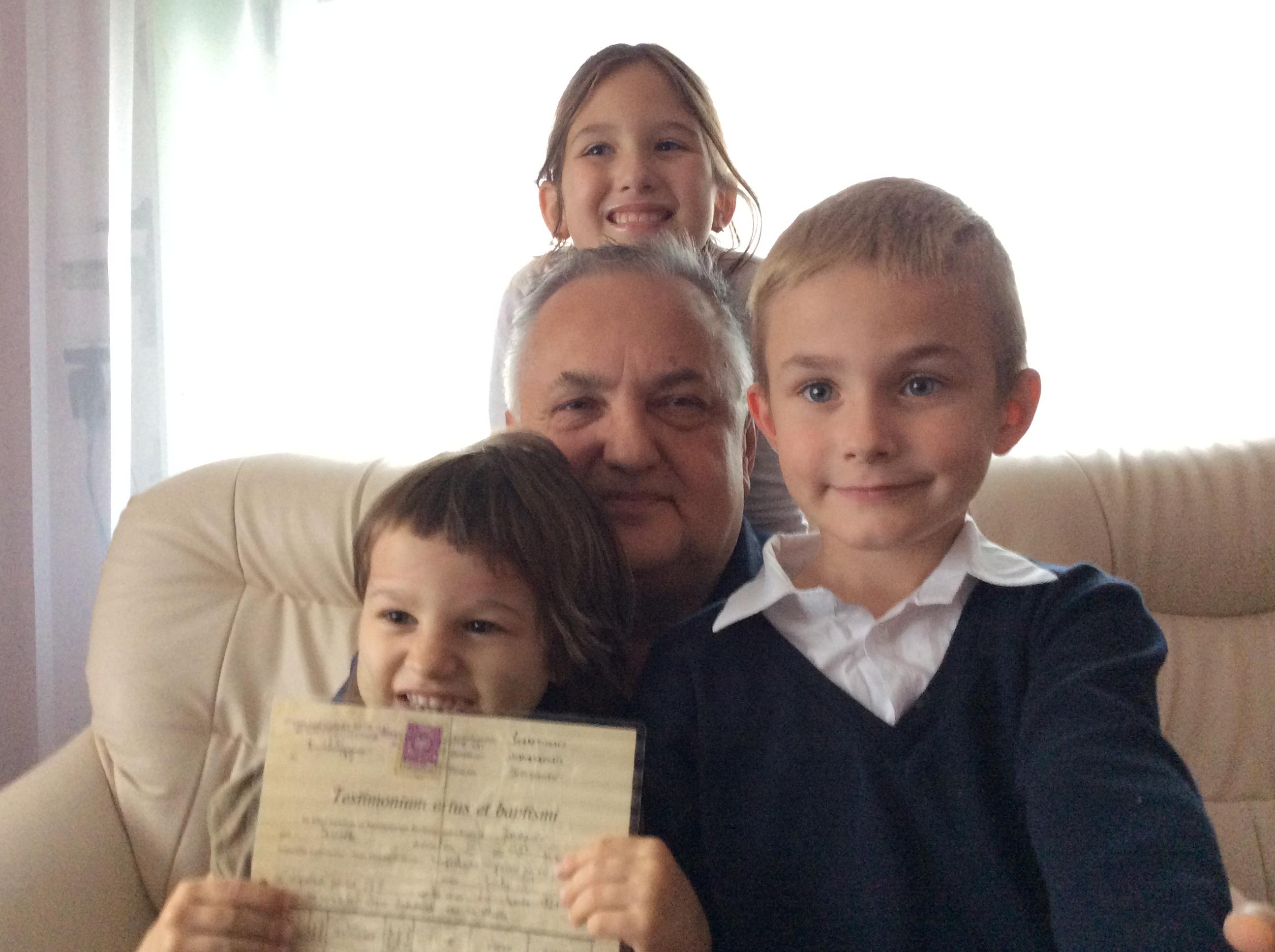 Jan Płoszczyca z wnukami. Ola trzyma metrykę urodzenia i chrztu pradziadka